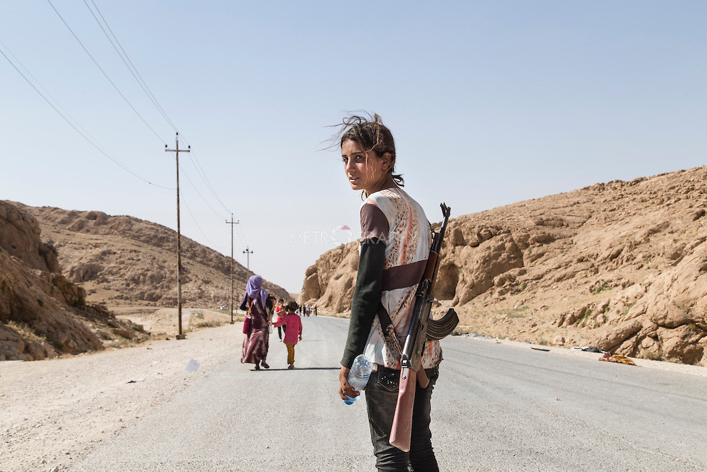 niña yezidi con fusil de asalto en el norte de iraq